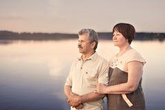 看日落的年长夫妇在湖河附近 库存图片