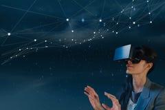 看星的VR耳机的妇女反对蓝色背景 免版税库存图片