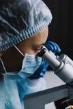 看显微镜的女性科学家 免版税库存照片