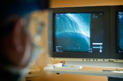 看显示器的外科医生在操作时 库存图片