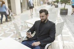看智能手机和微笑的酒吧大阳台的有胡子的衣服人 免版税库存图片