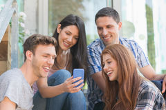 看智能手机外面在校园里的愉快的学生 库存图片
