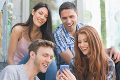 看智能手机外面在校园里的愉快的学生 免版税库存图片