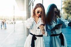 看智能手机屏幕的太阳镜的愉快的可爱的年轻女人,当走在城市时 穿戴在时髦的衣裳 库存图片