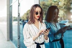 看智能手机屏幕的太阳镜的愉快的可爱的年轻女人,当走在城市时 穿戴在时髦的衣裳 免版税库存照片