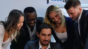 看智能手机屏幕,笑和谈论的现代年轻商人 库存图片