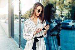 看智能手机的太阳镜的愉快的可爱的年轻女人 免版税库存照片