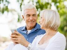 看智能手机的愉快的资深夫妇 免版税库存图片