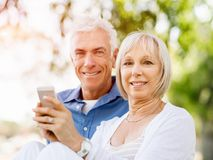 看智能手机的愉快的资深夫妇 免版税图库摄影