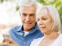 看智能手机的愉快的资深夫妇 库存图片