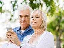 看智能手机的愉快的资深夫妇 库存照片