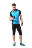 看智能手机的蓝色球衣T恤杉的年轻骑自行车者循环app 免版税库存图片