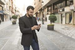 看智能手机的街道的人 免版税库存图片