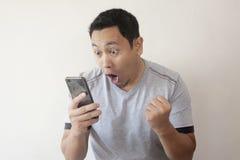 看智能手机的震惊愉快的人 免版税库存照片