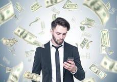 看智能手机,美元雨的有胡子的商人 库存照片