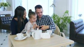 看智能手机,谈论和微笑的愉快的年轻家庭 股票录像