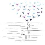 看有五颜六色的鸟的女孩海飞行在天空 免版税库存照片
