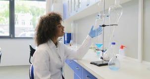 看有做化工实验的研究员队的非裔美国人的科学家妇女试管架  股票视频