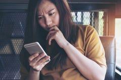 看有感觉重音的一名美丽的亚裔妇女巧妙的电话 免版税图库摄影