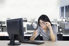 看有放大镜的妇女计算机 免版税库存图片