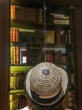 看有旧书的妇女玻璃门橱柜 免版税图库摄影