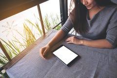 看有空白的白色桌面屏幕的一名美丽的亚裔妇女一台黑片剂个人计算机在桌上 库存照片