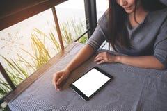 看有空白的白色桌面屏幕的一名美丽的亚裔妇女一台黑片剂个人计算机在桌上 库存图片