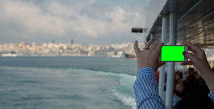 看有绿色屏幕的妇女水平的智能手机拍照片 关闭妇女有机动性的` s手射击  Istambul, Tur 免版税库存图片