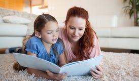 看杂志的母亲和女儿 免版税库存照片