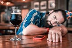 看杯美味的冷的黑啤酒的有胡子的深色头发的人 免版税图库摄影
