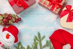 看板卡圣诞节新年度 与礼物箱子的滑稽的雪人,杉树分支,在多雪的蓝色木背景的圣诞老人头 库存图片