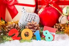 看板卡圣诞节新年度 在锥体、装饰圣诞节球和礼物盒附近的2018个五颜六色的图在雪和杉树branc 免版税图库摄影