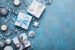 看板卡圣诞节问候 礼物盒、银色球、五彩纸屑、星和衣服饰物之小金属片在蓝色葡萄酒台式视图 平的位置 免版税图库摄影