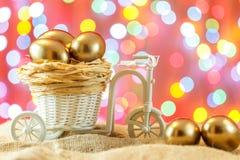 看板卡复活节 在自行车推车的金黄鸡蛋 鸡蛋 愉快的复活节 免版税图库摄影