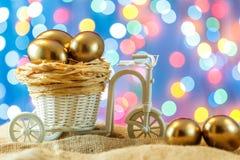 看板卡复活节 在自行车推车的金黄鸡蛋 鸡蛋 愉快的复活节 免版税库存图片