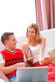 看板卡夫妇相信膝上型计算机坐的沙&# 库存照片