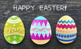 看板卡愉快的复活节 在老木背景的五颜六色的手工制造复活节彩蛋 免版税图库摄影