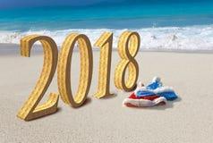 看板卡新年好 圣诞老人两个新年` s盖帽海滩和题字的2018年在沙子 库存图片