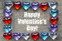 看板卡日愉快的华伦泰 框架由五颜六色的玻璃心脏做成在与文本的老木背景 免版税图库摄影