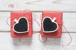 看板卡s华伦泰 有晒衣夹的两个红色礼物盒作为与空间的心脏在黑板的文本的在木轻的背景 名列前茅v 图库摄影