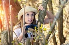 看某事的美丽的年轻远足者妇女在森林 免版税库存照片