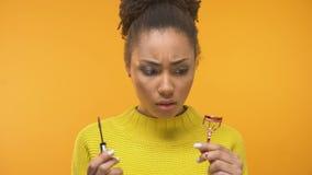 看染睫毛油和睫毛卷发的人的被迷惑的黑人妇女,需要构成技巧 影视素材