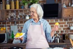 看柠檬的妇女在厨房里 免版税库存照片