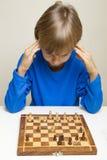 看棋盘和考虑接下来的步骤的小孩 免版税图库摄影
