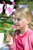 看棒棒糖的美丽的小女孩 免版税库存照片