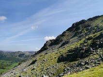 看横跨对遥远的登山人的岩石山坡 免版税库存图片