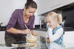 看母亲的女孩烹调在厨房里 库存图片