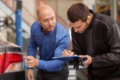 看汽车尾灯的技工和顾客 免版税库存照片