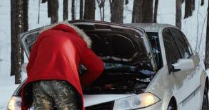 看汽车的引擎人 修理打破的汽车的人 驾驶的冬天,在一条多雪的乡下公路的麻烦 股票录像