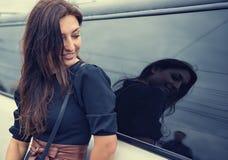 看汽车玻璃的反射的美丽的妇女人 免版税库存图片